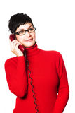 Secretary in red. Beautiful young woman with charming big green eyes is bearing modern glasses and receiving calls on a landline phone Royalty Free Stock Photos