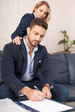 Secretary seducing boss from behind in office. Seduction, rich young businessman write contract Royalty Free Stock Photos