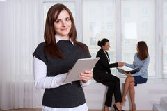 Secretary smiling woman reads information from the tablet Royalty Free Stock Photography