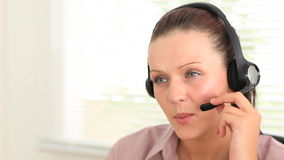 Secretary speaking on the phone with an headset stock video footage