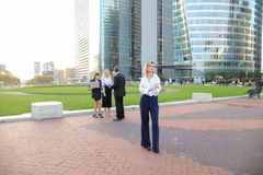 Secretary looking at camera with team members background in La D. Secretary standing in La Defense Paris and looking at camera near speaking employees with boss Stock Image