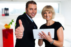 Secretary with a tablet posing with her successful boss Royalty Free Stock Images