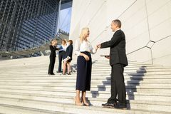 Secretary talking with boss keeping tablet on stairs with employ. Boss keeping tablet and speaking with blonde secretary on stairs with biz partners in Stock Image