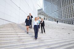 Secretary talking with boss keeping tablet on stairs with employ. Boss keeping tablet and speaking with blonde secretary on stairs with biz partners in Stock Images