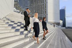 Secretary talking with boss keeping tablet on stairs with employ. Boss keeping tablet and speaking with blonde secretary on stairs with biz partners in Royalty Free Stock Photos
