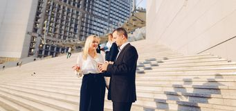 Secretary talking with boss keeping tablet on stairs with employ. Boss keeping tablet and speaking with blonde secretary on stairs with biz partners in royalty free stock photography