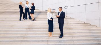 Secretary talking with boss keeping tablet on stairs with employ. Boss keeping tablet and speaking with blonde secretary on stairs with biz partners in stock photography
