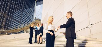 Secretary talking with boss keeping tablet on stairs with employ. Boss keeping tablet and speaking with blonde secretary on stairs with biz partners in royalty free stock image