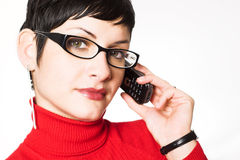 Secretary talks on mobile. Beautiful young woman with charming big green eyes is bearing modern glasses and receiving calls on a mobile phone Royalty Free Stock Images