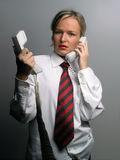 Secretary in trouble with phones Royalty Free Stock Images