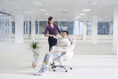 Secretary Unwrapping Businessman In New Office. Secretary unwrapping businessman on chair in empty office space Royalty Free Stock Photos