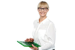 Secretary using large green calculator. Finger on subtract key Stock Photo