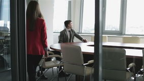 Secretary woman in a red jacket brings coffee for a boss. Two businessmen are sitting at a table in a meeting room behind a glass wall stock footage