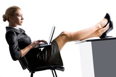 Secretary working. Image of elegant secretary typing on laptop with her legs on table Royalty Free Stock Photo