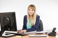 Secretary working in the computer, close the folder with the documents is Stock Images