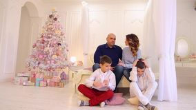 Secretismo dos irmãos gêmeos e vindo acima com mimar olhando seus pais e sentando-se no assoalho no quarto com Natal filme
