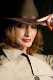 Secretive Beauty. A beautiful woman in a trenchcoat and fedora hat, looking behind her in a secretive way royalty free stock image