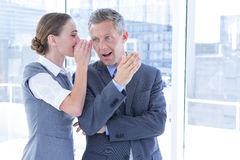 Secretive business colleagues whispering Stock Image
