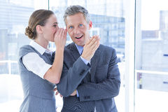 Secretive business colleagues whispering Stock Images