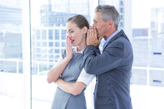 Secretive business colleagues whispering Royalty Free Stock Photography