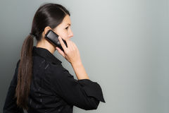 Secretive businesswoman talking on her mobile Royalty Free Stock Photo