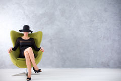 Secretive charm of a modern vamp woman. Seductive young woman in a black dress and a hat covering her eyes, sitting in an olive green egg chair Stock Images