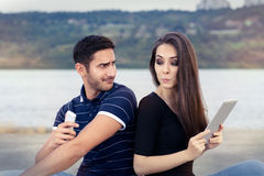 Secretive Couple with Tablet and Smartphone. Young adult couple has privacy problems with modern technology royalty free stock images