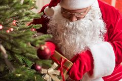 Secretive Santa Claus laying gift box to fir-tree Royalty Free Stock Photo