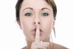 Secretive Young Woman with Finger on Lips. Attractive Secretive Young Woman with Finger on Lips royalty free stock photography