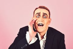 Secretly between you and me. Performance art and pantomime. Actor acting secret. Mime artist. Mime with face paint. Man. With mime makeup. Theatre actor miming stock images