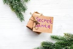 Secreto Papá Noel del juego de la Navidad Caja de regalo cerca de la rama spruce en el copyspace de madera blanco de la opinión s imágenes de archivo libres de regalías