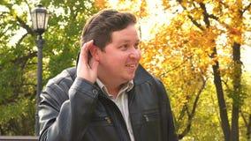 Secreto que escucha del hombre en Autumn Park, al aire libre almacen de metraje de vídeo