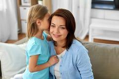 Secreto susurrante de la hija a mimar en casa imagen de archivo libre de regalías