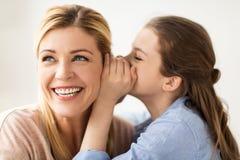 Secreto susurrante de la muchacha feliz a su madre Imagen de archivo