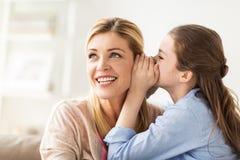 Secreto susurrante de la muchacha feliz a su madre en casa Fotografía de archivo