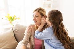 Secreto susurrante de la muchacha feliz a su madre en casa Imágenes de archivo libres de regalías