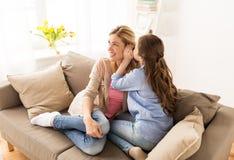 Secreto susurrante de la muchacha feliz a su madre en casa Fotos de archivo libres de regalías