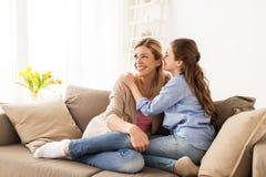 Secreto susurrante de la muchacha feliz a su madre en casa Fotos de archivo