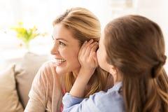 Secreto susurrante de la muchacha feliz a su madre en casa Fotografía de archivo libre de regalías