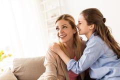 Secreto susurrante de la muchacha feliz a su madre en casa Imagen de archivo