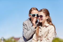 Secreto susurrante de la muchacha feliz a su oído de los amigos Foto de archivo