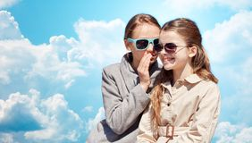 Secreto susurrante de la muchacha feliz a su oído de los amigos Fotos de archivo libres de regalías