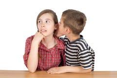 Secreto susurrante del muchacho en el oído de la hermana aislado en blanco Fotos de archivo libres de regalías