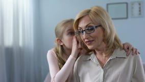 Secreto susurrante a la abuela hermosa, confianza del grandkid femenino divertido de la familia almacen de video