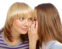 Secretos susurrantes de la muchacha en el oído de su mamá Imagen de archivo libre de regalías