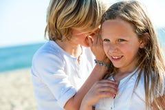 Secretos susurrantes del muchacho a la muchacha al aire libre. Foto de archivo