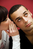 Secrets. Young couple: she is telling his boyfriend some cool gossip Royalty Free Stock Photos