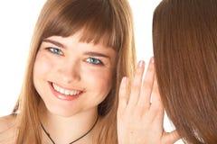 secrets heureux d'amies indiquant deux jeunes Image libre de droits
