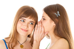 secrets heureux d'amies indiquant deux jeunes Images libres de droits