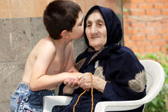 Secrets between kid and granny. Little kid whispers to old granny in summer backyard sharing secrets Royalty Free Stock Images